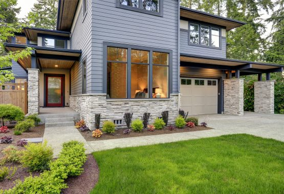 Luxurious new home with curb appeal. Trendy grey two-story exterior in Bellevue with large picture windows stone foundation veneer covered porch and concrete pathway. Northwest USA